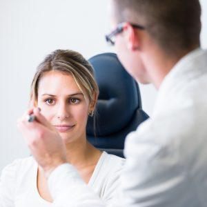 Oftalmologista examinando e explicando para paciente o que é crosslinking