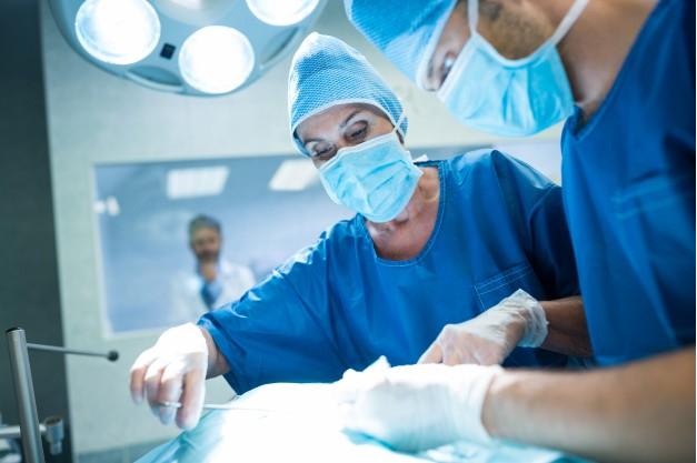 dois médicos uniformizados realizando cirurgia de vitrectomia em paciente