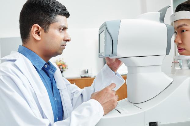 médico usando camisa azul e avental branco realizando exame em paciente com camisa cinza dentro de um consultório
