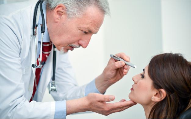 médico de avental branco e gravata vermelha examinando olhos de paciente usando uma pequena lanterna dentro de seu consultório
