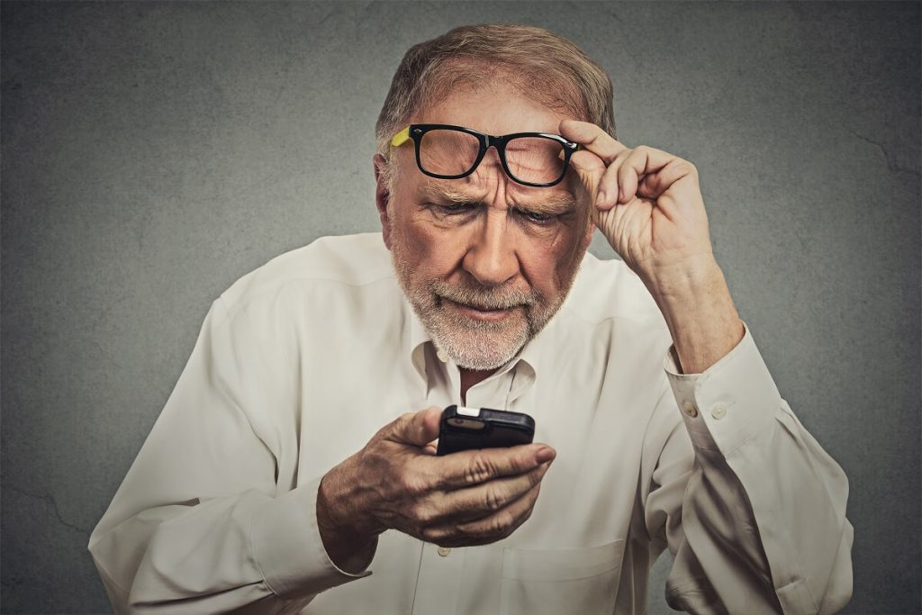 idoso com óculos tendo dificuldades para enxergar de perto
