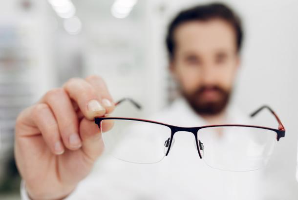 médico segurando par de óculos em primeiro plano e ao fundo sua imagem aparecendo embaçada