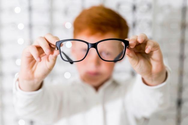 criança ruiva segurando óculos que aparece e, destaque em primeiro plano e ao fundo sua imagem embaçada