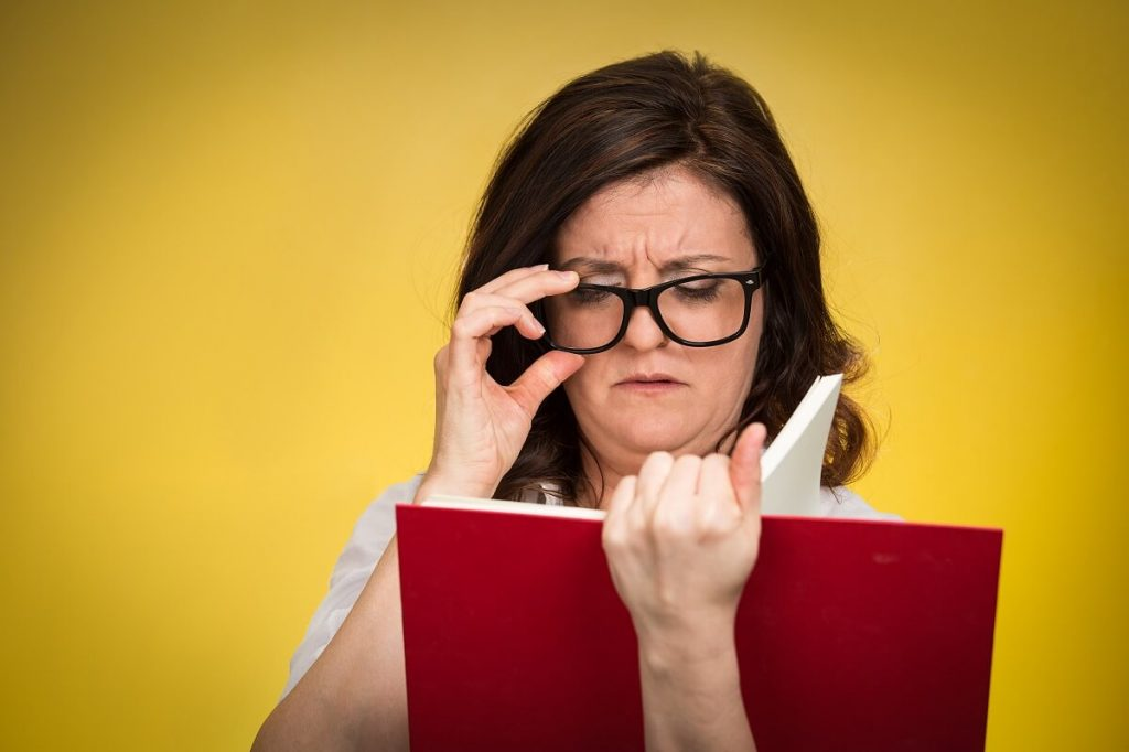 Mulher lendo sobre as diferenças entre miopia hipermetropia e astigmatismo