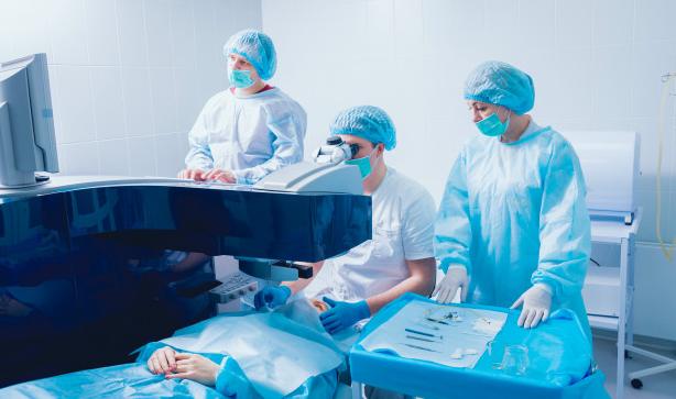 equipe de médicas usando uniformes azul e branco se preparando para realizar cirurgia de catarata