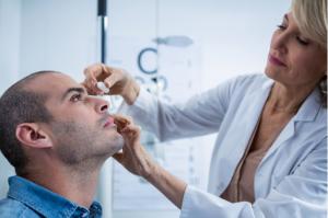 médica usando jaleco branco aplicando colírio antibiótico em paciente homem dentro de um consultório