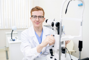 oftalmolista ruivo usando óculos e jaleco branco em seu consultório preparando seu equipamento para realizar retinografia simples