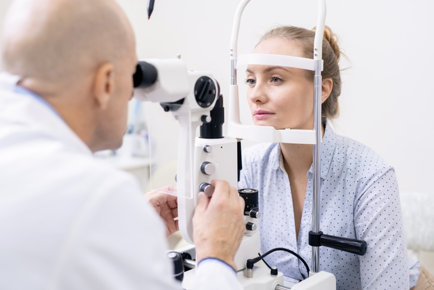 médico careca usando avental branco realizando exame de retinografia simples em paciente loira usando camisa azul dentro de seu consultório