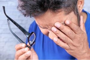 homem usando camiseta azul retirando os óculos e levando a mão aos olhos