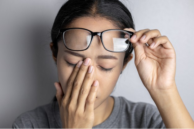 mulher de costas para uma parede branca retirando par de óculos do resto e levando a mão aos olhos