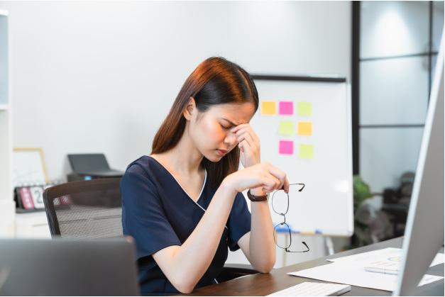 mulher sentada em frente a uma mesa dentro de um escritório retira os óculos e leva a mão aos olhos