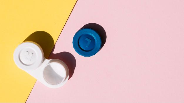 em uma mesa laranja e rosa encontra-se um pote de lente de contato ao lado de uma de suas tampas de cor azul