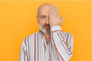 homem idosos de barba e camisa listrada de costas para parede laranja tampando metade do rosto com as mãos