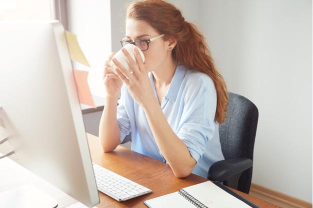 mulher de óculos tomando café enquanto está sentada a uma mesa de frente para um monitor
