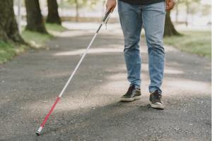 imagem das pernas e bengala de uma pessoa com deficiência visual caminhando no parque
