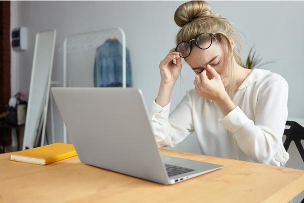 mulher sentada a uma mesa de frente para um laptop leva as mãos ao rosto