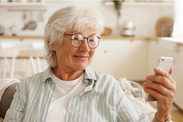 idosa sentada em um sofá sorri enquanto usa um par de óculos para enxergar seu celular
