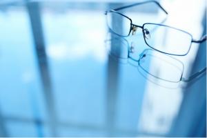 em uma mesa de vidro que reflete as janelas de um prédio está um par de óculos de grau