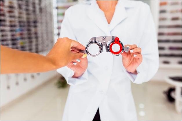 técnica dentro de ótica usando um avental branco entrega um aparelho para exames oftalmológico à pessoa a sua frente