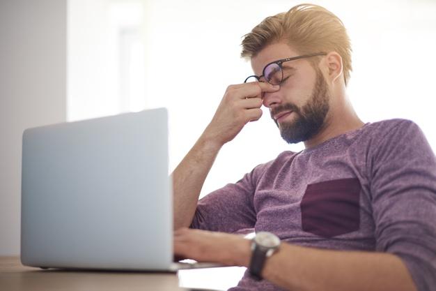Um homem diante do computador está tocando seus olhos por baixo dos óculos