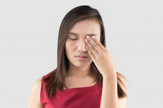 Mulher tocando os olhos por ter doenças das pálpebras