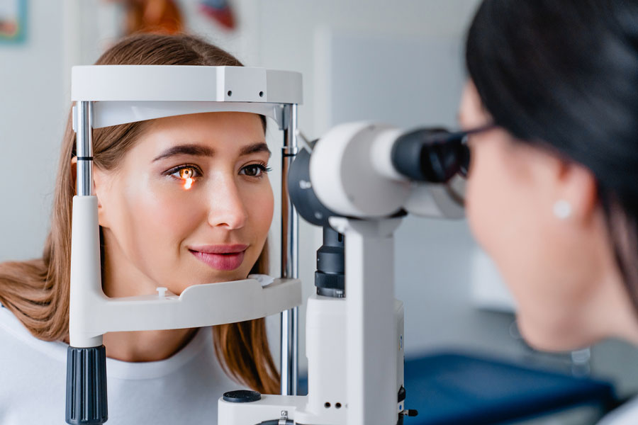 Oftalmologista em ambulatório com equipamento moderno, realizando procedimento de fotocoagulação a laser em paciente.