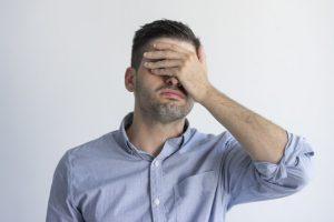 Homem de camisa azul de costas para fundo branco levando a mão à cabeça tampando os olhos