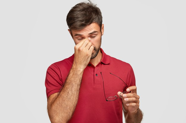 homem de camisa polo vermelha retira os óculo e leva a mão aos olhos