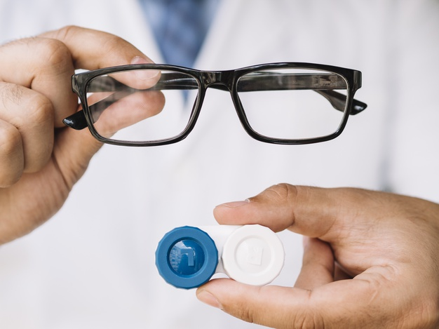 médico exibe par de óculos e compartimento para lentes na cor azul e branca