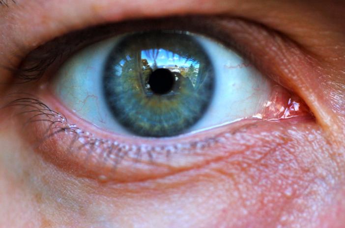 imagem ampliada do olho aberto de íris cor azul de uma pessoa