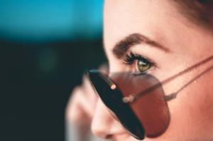 imagem ampliada do rosto de uma mulher abaixando um pouco o óculos de sol