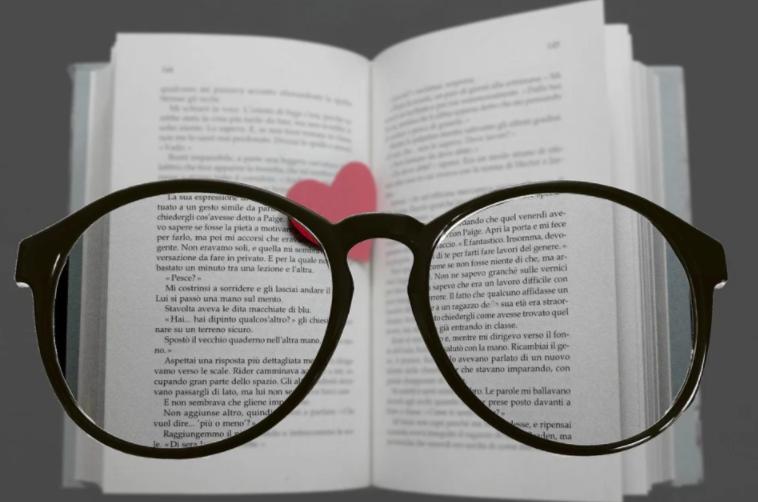 Óculos sobre um livro aberto.