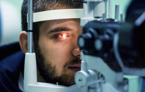 Homem à frente de uma máquina realizando check-up oftalmológico
