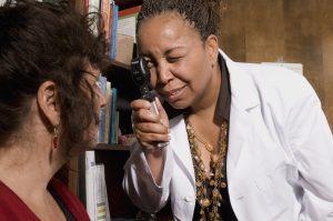 mulher apontando aparelho de exame de olho para outra mulher, com uma estante de livro atrás - exame de fundo de olho