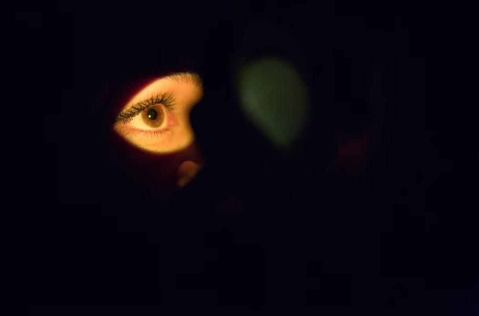 imagem de um olho iluminado com todo o resto escuro, simulando um exame para detecção de hordéolo interno