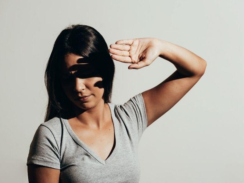Mulher cobrindo os olhos com a mão por dificuldade de olhar para a luz: o que é fotofobia