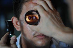 Pessoa tendo o olho examinado com uma lupa de aumento